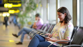 Airport Waiting Area. Young woman using a digital tablet in airport waiting area stock footage