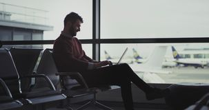 In the airport in a waiting aria businessman working on his notebook till waiting for the flight, then he finished the. Work and go to the boarding. 4k .shot on stock footage