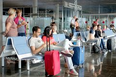 Airport waiting lounge with passengers and luggage. Passengers waiting for their flight in the sitting area by a gate at LPA Airport, Las Palmas de Gran Canaria Royalty Free Stock Photography