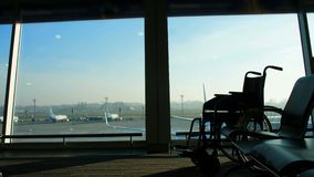 At the airport, in the waiting room, against the background of the window overlooking the aircraft and the runway, is a. Wheelchair, you can see its outlines stock video