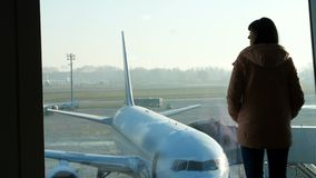 At the airport, in the waiting room, against the background of a window overlooking the airplanes and the runway, stands stock footage