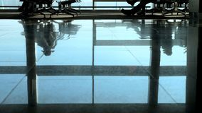 Airport, waiting room, on the tiled floor are reflected figures of people. The dark figures of people hurry back and. Forth stock video footage