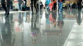 Airport, waiting room, on the tiled floor are reflected figures of people. figures of people hurry back and forth. Airport, waiting room, on the tiled floor are stock footage