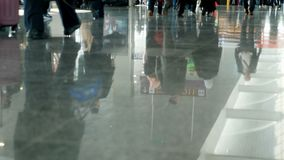 Airport, waiting room, on the tiled floor are reflected figures of people. figures of people hurry back and forth. Airport, waiting room, on the tiled floor are stock video footage