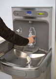 Airport water bottle fill station in use. This fountain serves a dual purpose. You can drink and fill a water bottle when travelling to avoid getting dehydrated royalty free stock photos