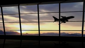Airport window. With airplane flying at sunset Stock Image