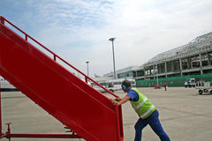 Airport worker. Pushing a set of stairs for boarding an airplane Stock Image