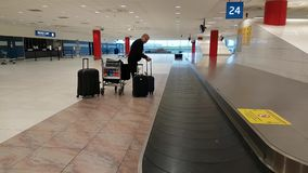 Airport worker collects lost luggage from the conveyor stock footage