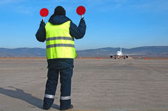 Airport worker directing. Airplane at an airport Royalty Free Stock Photography