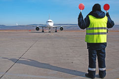 Airport worker directing. Airplane at an airport Royalty Free Stock Image