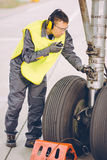 Airport worker mechanic. Service maintenance chassis tire Royalty Free Stock Photos