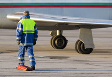 Airport worker runway airplane. An airport worker is stabilizing the airplane tires on the airport runway after landing Stock Images