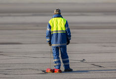 Airport worker runway airplane. An airport worker is waiting for an airplane to land and stabilize its tires on the airport runway Royalty Free Stock Image