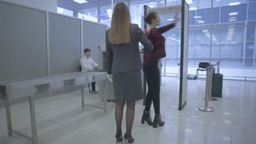The airport worker scans a woman`s body with hand scanner in the airport stock video