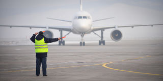 Airport worker signaling. Airport worker directing an airplane as it arrived stock photos