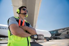 Airport worker in sunglasses and headphones crossing arms royalty free stock image