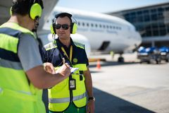 Airport worker in sunglasses showing notes to colleague stock photo