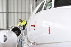 Airport workers check an aircraft for safety in a hangar Royalty Free Stock Image