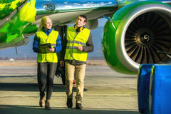 Airport workers handling airplane Stock Images