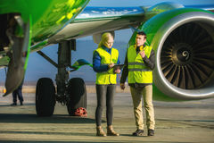 Airport workers handling airplane Stock Photo