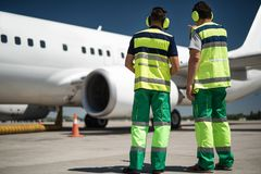 Airport workers looking at plane and discussing departure stock photography