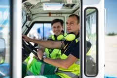 Airport workers sitting in the car. Photoshoot during work. Serious men in headphones with microphone sitting behind the wheel. Smiling colleague on blurred royalty free stock photos