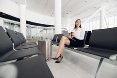 Airport Young Female Passenger On Smart Phone And Laptop Sitting In Terminal Hall While Waiting For Her Flight. Air Royalty Free Stock Photography
