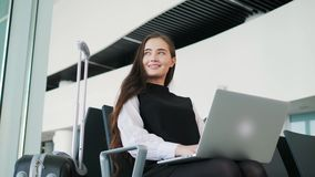 Airport Young female passenger on smart phone and laptop sitting in terminal hall while waiting for her flight, work. Airport Young female passenger on smart stock footage