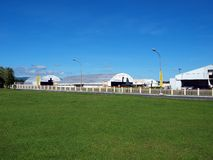 AirportGreenHangars. Semi-cylinder hangars in background at airport green field royalty free stock photo