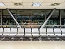 Airport waiting area. Empty benches at an airport waiting area inside a connection bridge at night Royalty Free Stock Images