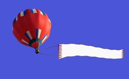Airship with banner. Colorful hot air balloon towing blank banner with copy space in blue sky Royalty Free Stock Image