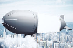 Airship on city background side Royalty Free Stock Image