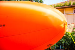 Airship. An orange airship floats on the ground Royalty Free Stock Photo