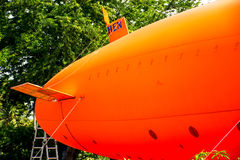 Airship. An orange airship floats on the ground Royalty Free Stock Image