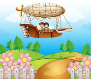 An airship passing the hills with kids royalty free stock image