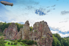 Airship, zeppelin flying over the Externsteine. Taking photo  taken in front of  dramatic sky. Markant sandstone rock formation in the Teutoburg Forest Royalty Free Stock Photos