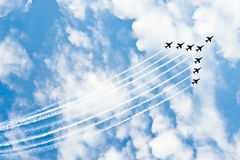 Aerobatic team in formation. Aerobatic team flying in formation trailing jet streams with blue sky and cloudscape background Royalty Free Stock Images