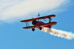Airshow memorável Voo vermelho do biplano de Stearman para a câmera ao arrastar o fumo na exposição Fotos de Stock