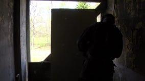 airsoft的球员在军服的有武器的在位置在窗口附近在一个被破坏的房子 股票录像