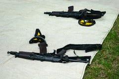 Airsoft automatiskt vapen och gulingsäkerhetsexponeringsglas som ligger på det fab arkivfoton