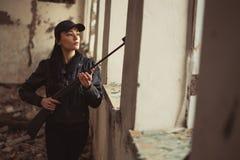 Airsoft-Frauensoldat mit einem Gewehr, das strikeball im Altbau spielt lizenzfreie stockbilder