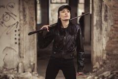 Airsoft-Frauensoldat mit einem Gewehr, das strikeball im Altbau spielt stockfoto