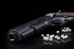Airsoft pistol with bb bullets on black glossy surface. Airsoft pistol with bb bullets on dark glossy surface and black background Stock Photo
