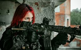 Airsoft red-head woman in uniform with machine gun standing on balkony. Close up soldier aim at the sight