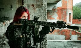 Airsoft red-head woman in uniform with machine gun standing on balkony. Soldier aim at the sight
