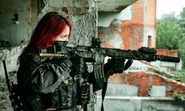 Airsoft red-head woman in uniform with machine gun standing on balkony. Soldier aim at the sight. Close up side view