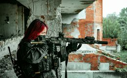 Airsoft red-head woman in uniform with machine gun standing on balkony. Soldier aim at the sight. Side view