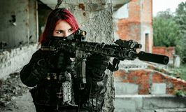 Airsoft red-head woman in uniform with machine gun standing on balkony. Soldier aims at the sight