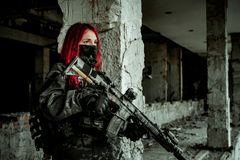 Airsoft red-head woman in uniform and put down machine gun. Close up soldier standing on balkony. Horizontal photo side view