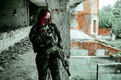 Airsoft red-head woman in uniform and put down machine gun. Soldier standing on balkony. Horizontal photo
